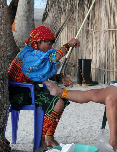 Kuna woman dressing up a tourist's ankle in their typical beads